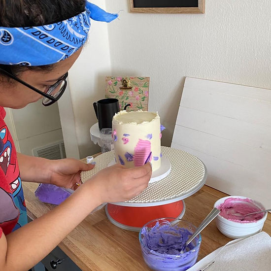 The owner of The Truth Bakes decorating a birthday cake