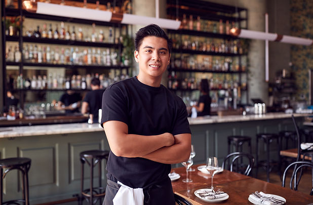 portrait-of-male-waiter-standing-in-bar-