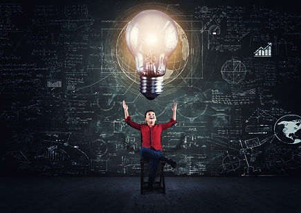 Photo of student gesturing toward large lightbulb over his head