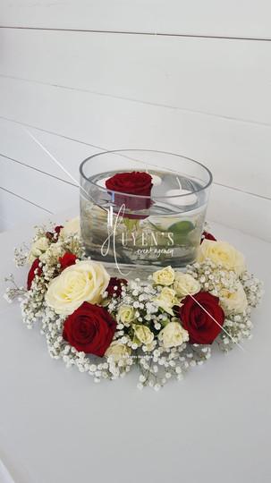 Couronne florale sur son vase cylindrique et ses bougies flottantes