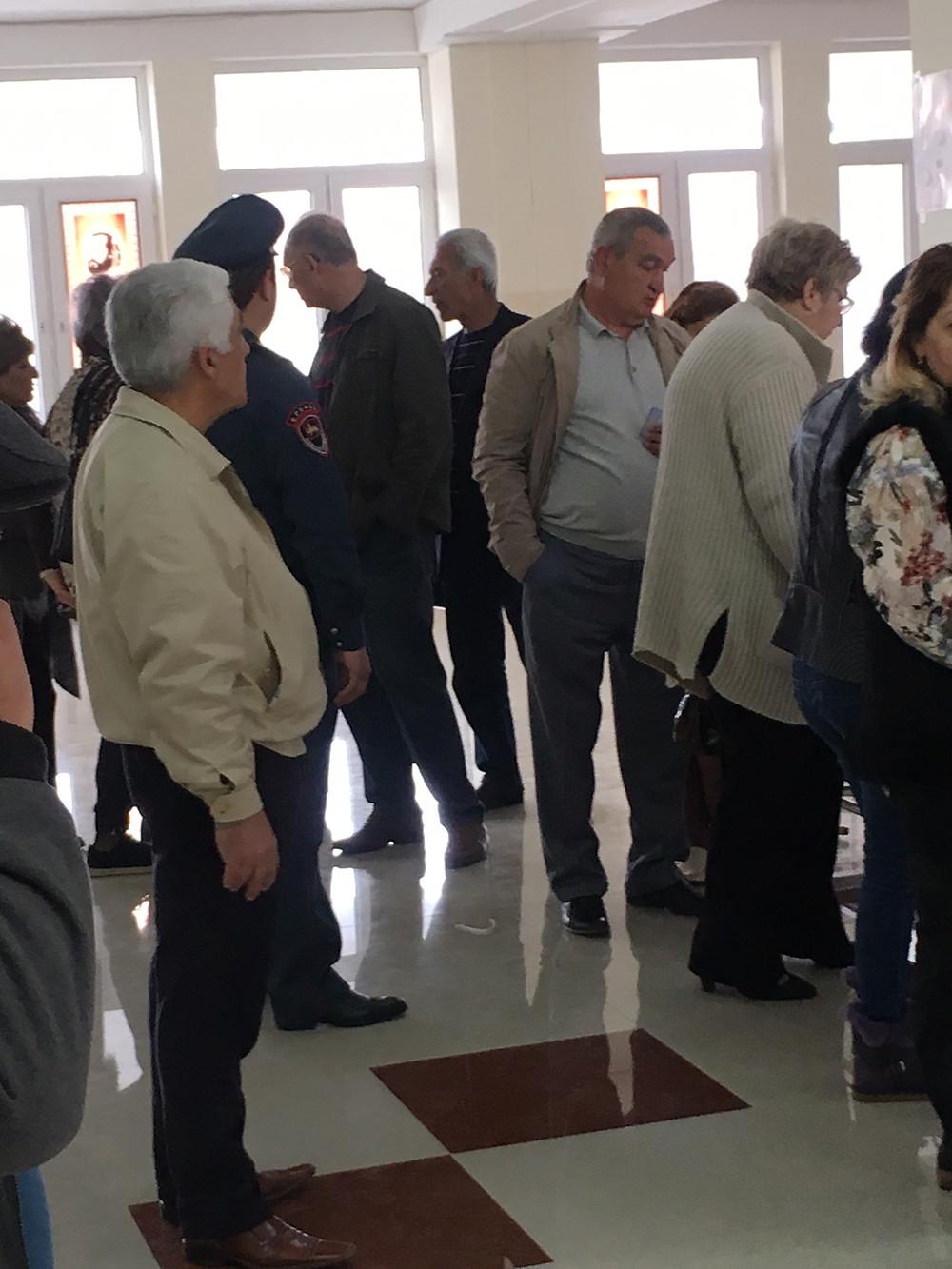 """Fil d'attente des électeurs, représentant de parti politique faisant """"la police"""" dans le bureau. A côté d'un vrai policier. Bureau de vote n°1 de Davtashen, Erevan, Arménie, 2 avril 17"""