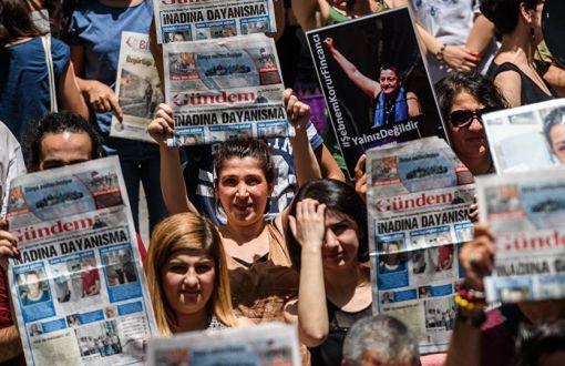 Hommes et femmes tenant le journal Ozgur Gundem en signe de solidarité avec le journal persécuté