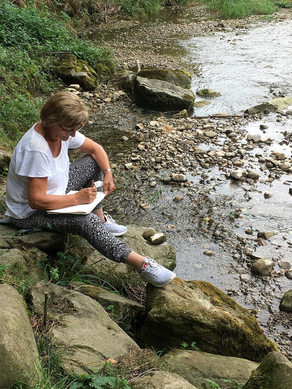 Elisabeth hockt am Ufer und lässt schon den Farbstift übers Papier wandern.