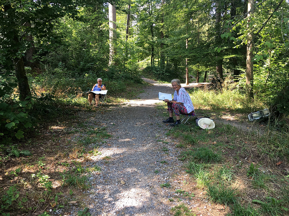 Margret und Emma sitzen am Wegrand, ins Gespräch vertieft