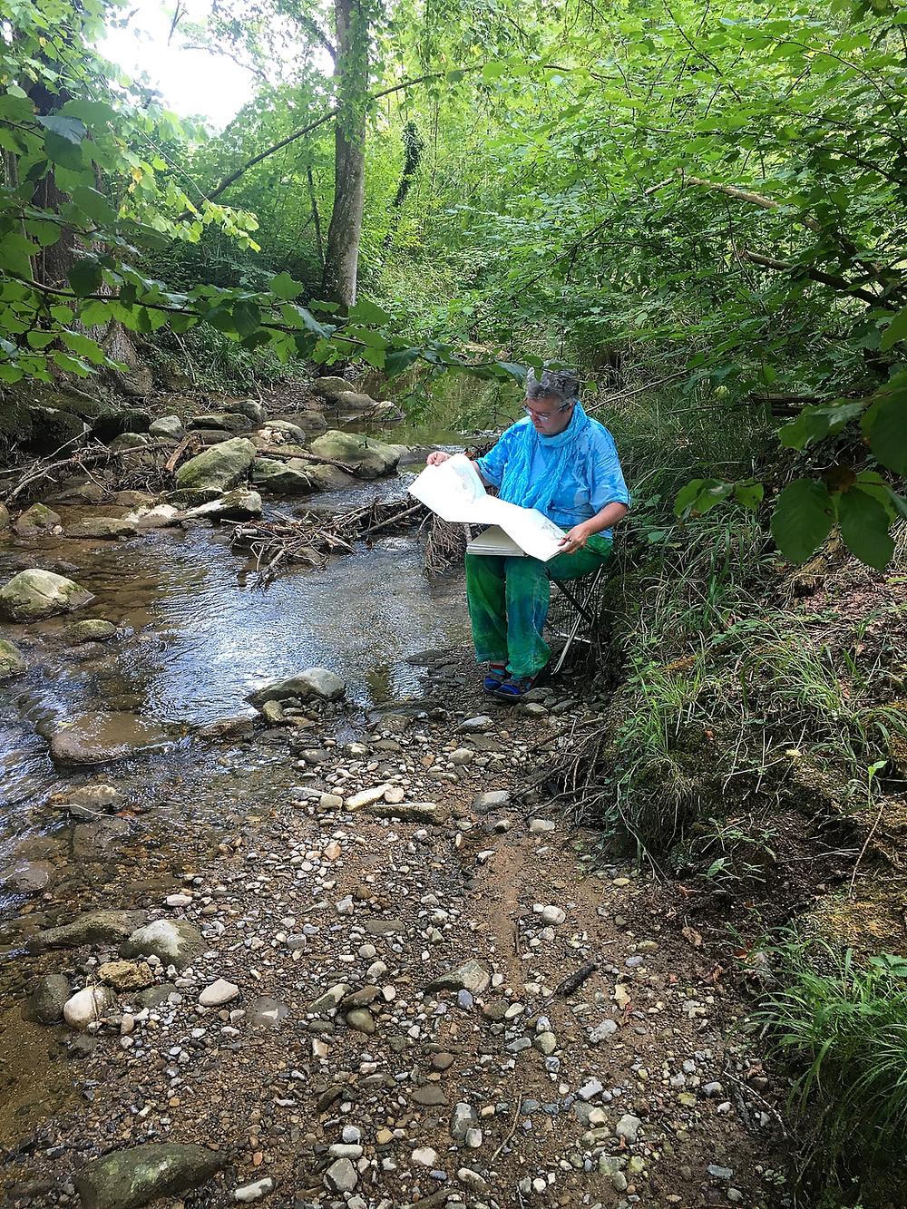 Versteckt zwischen grüner Uferbewachsung ist Christine zu entdecken, nah am Wasser und voller Konzentration.