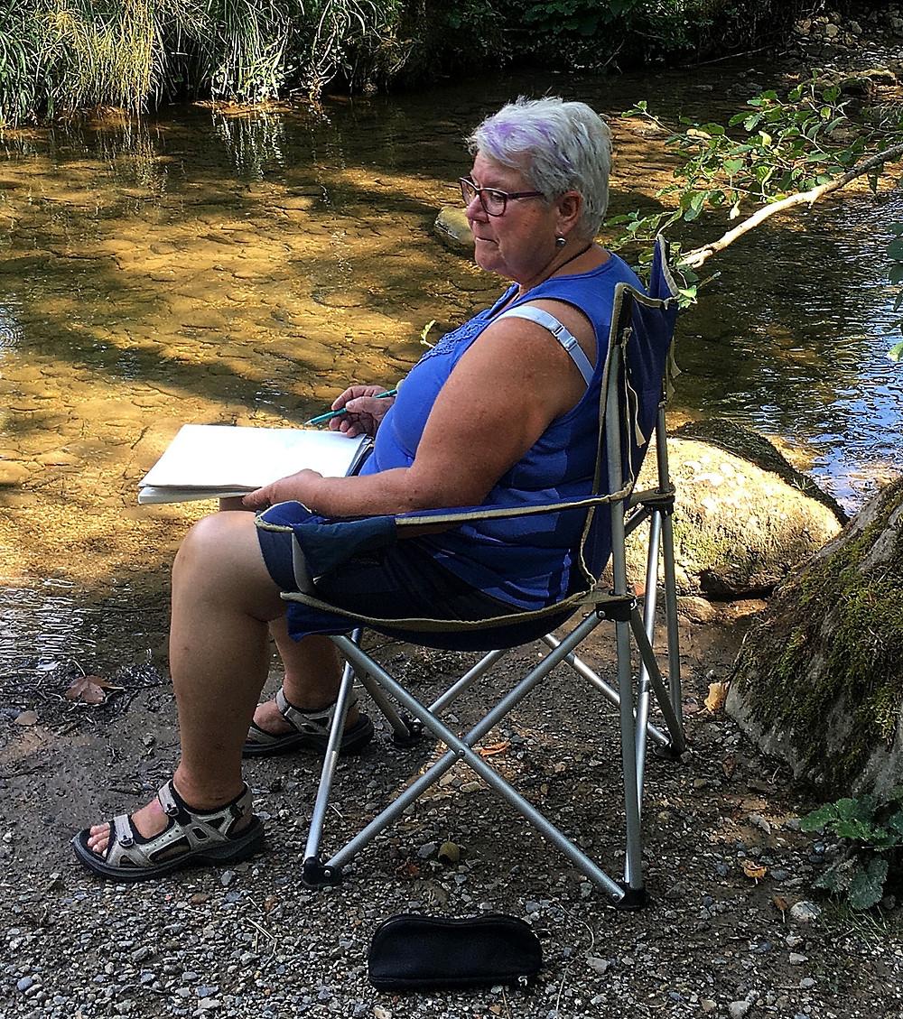 Margret hat den bequemsten Stuhl. die Umgebung einem prüfenden Blick unterwerfend sucht sie nach einem Motiv.