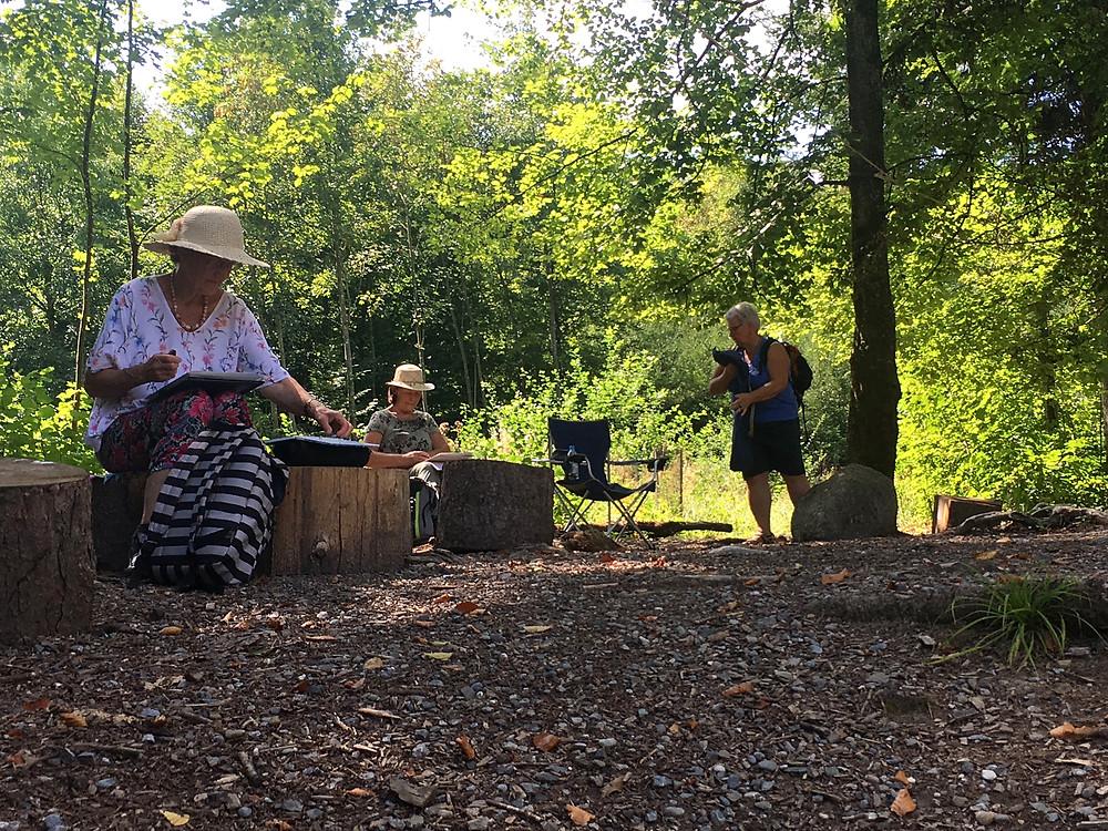 Emma, Erika und Margret richten sich ein bei einer leicht erhobenen Grillstelle im Wald