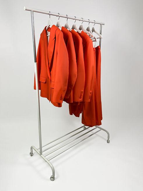 Designer Regenjacke und passende Regenhose in orange auf Kleiderständer