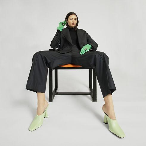 Model trägt Designer Regenjacke und passende Regenhose in schwarz sitzend auf einem Stuhl