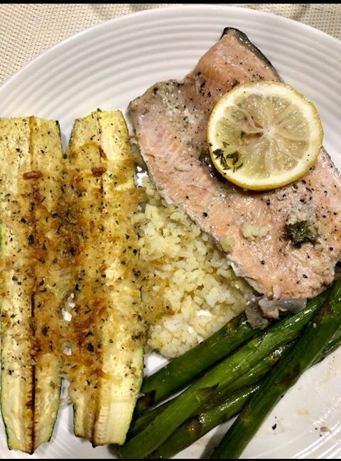 Baked trout in foil with garlic butter, salt, pepper, fresh lemon and a little olive oil