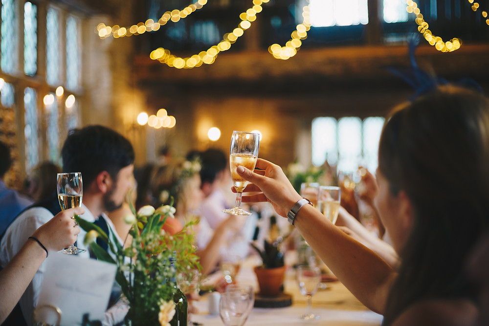 People at a wedding sitting at a table raising a toast.