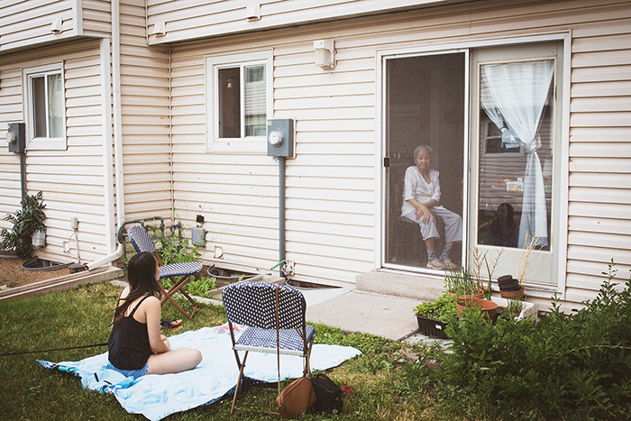 Granddaughter looks at grandmother in the home through screen door.