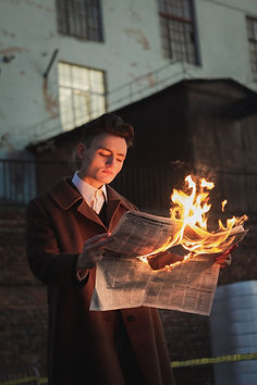 man-reading-burning-newspaper-3278364.jp