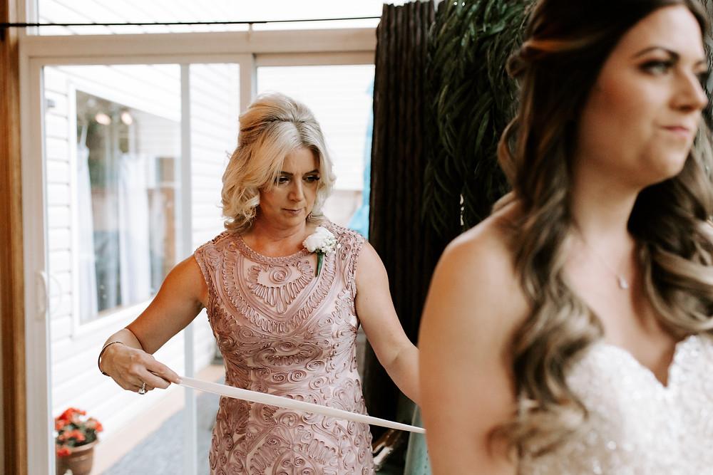 calgary bride mom putting on dress