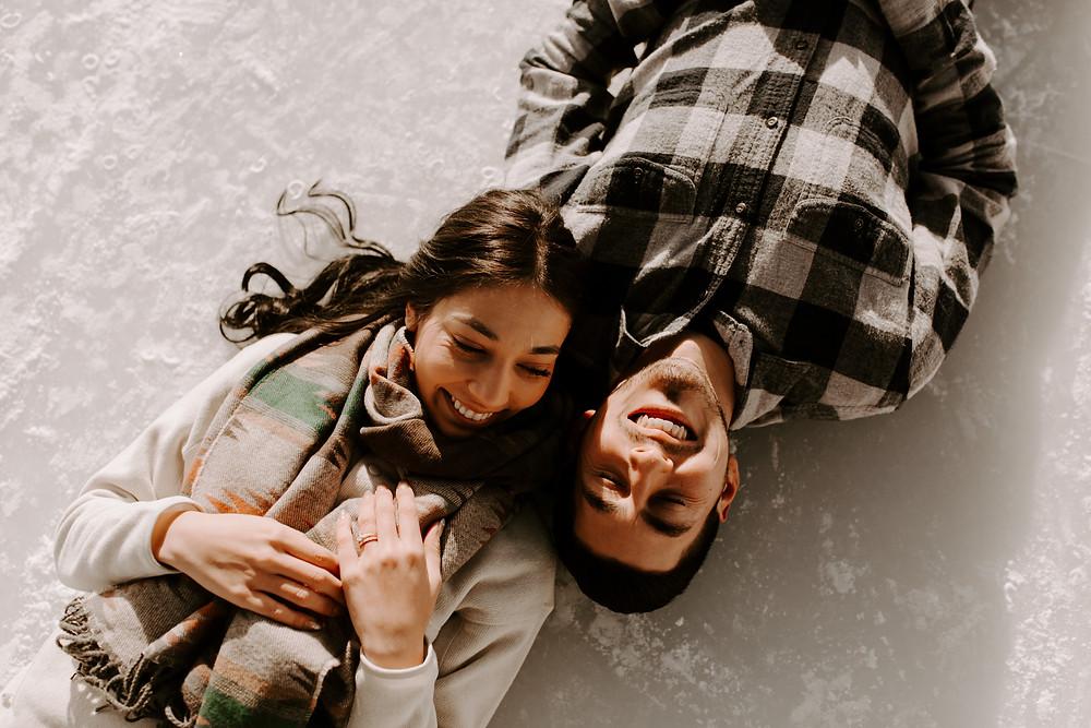 couple laying on ice lake minnewanka banff