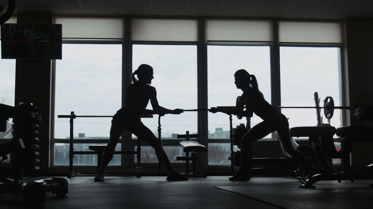 silhouette-of-two-womans-pulling-a-rope-
