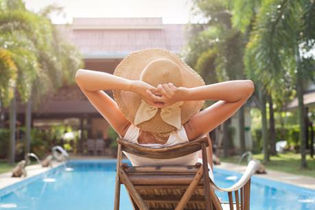 woman in hat taking sunbath near swimmin