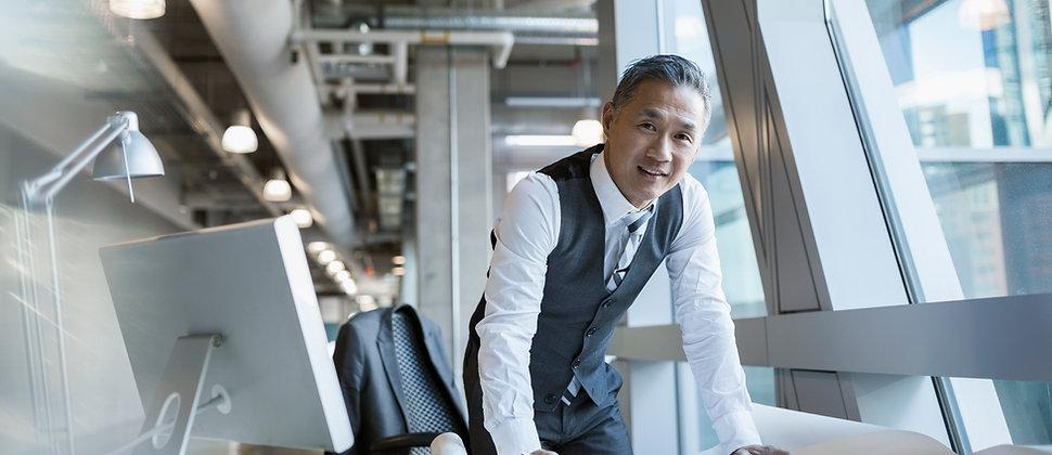Image d'un homme d'affaire dirigeant accoudé à son bureau - JB consultant - Coaching de dirigeant à Paris et Toulouse - Performance organisationnelle et développement stratégique