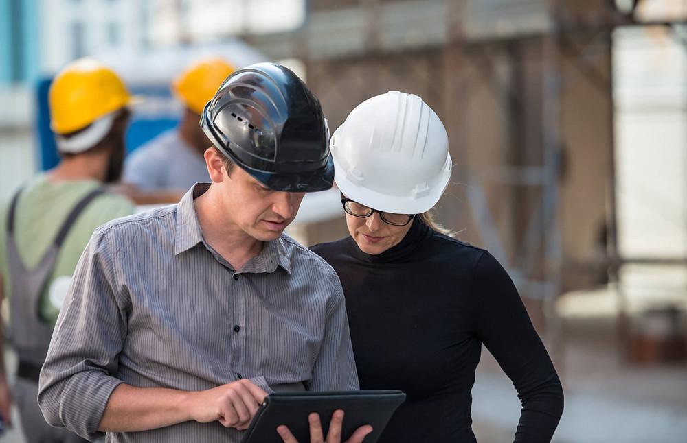 engenheiro homem e mulher com capacete preto e outro branco, com uso de tablet e apontamento eletronico
