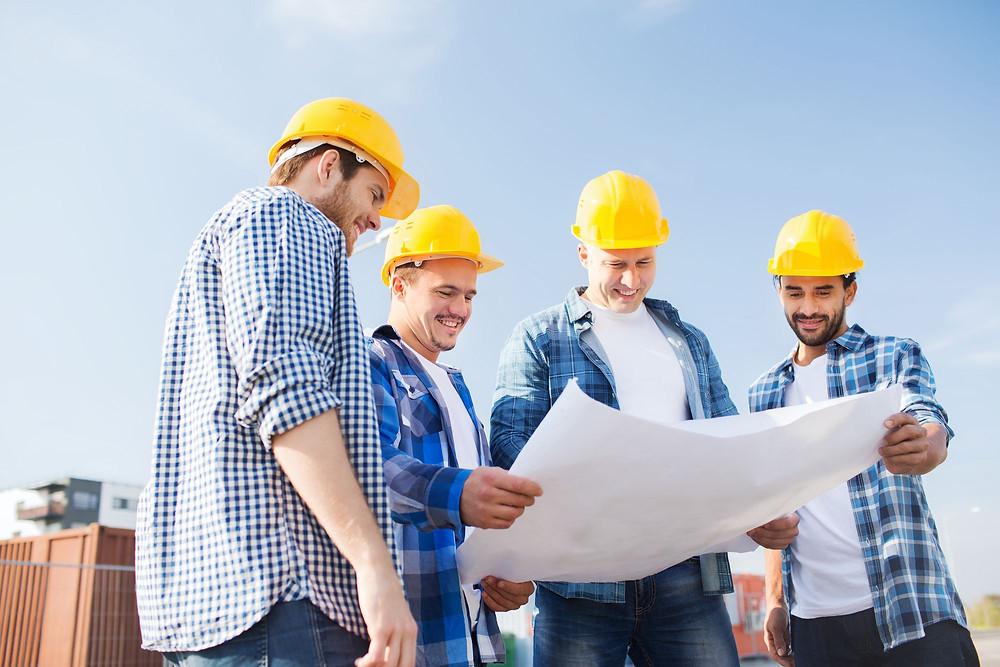 equipe na construção conferindo plano de obra antes de migrarem para um apontamento eletrônico SImova