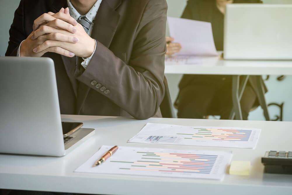 Gestor de projetos beneficiado pelo apontamenot eletronico, usando terno e gravata. graficos impressos para uma análise até migrar para Simova