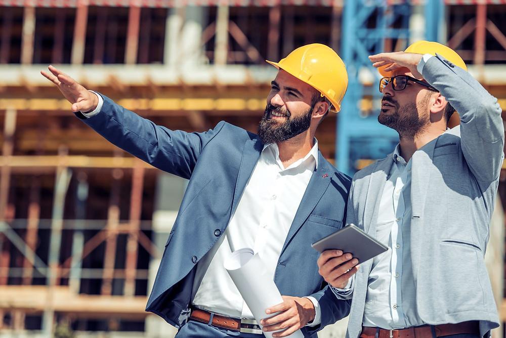 engenheiros discutindo projeto na obra vendo smartphone, por meio de apontamento eletrônico