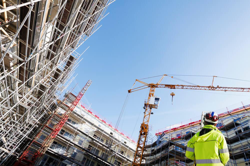 operario na construção apontando obra com SImova app