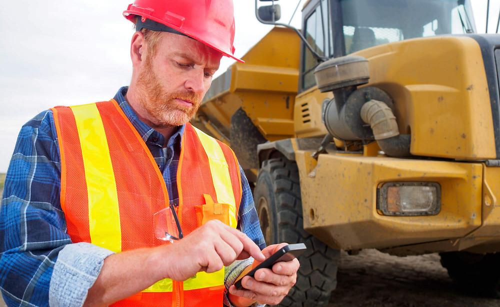 tecnico em campo apontando com smartphone. trator amarelo. capacete vermelho