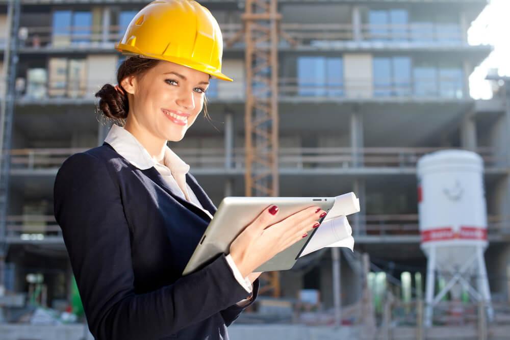 mulher operario de consturção civil apontando eletronicamente através de tablet na construcao civil