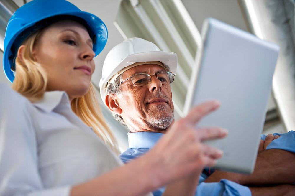 apontando eletronicamente atividades. dois engenheiros em obra com tablet. capacete azul e capacete branco.
