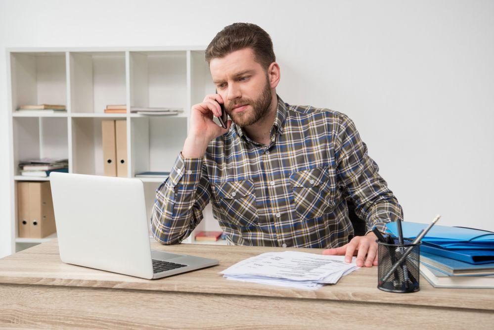 gestor seguindo o progresso de de obra e contactando através de smartphone as equipes externas