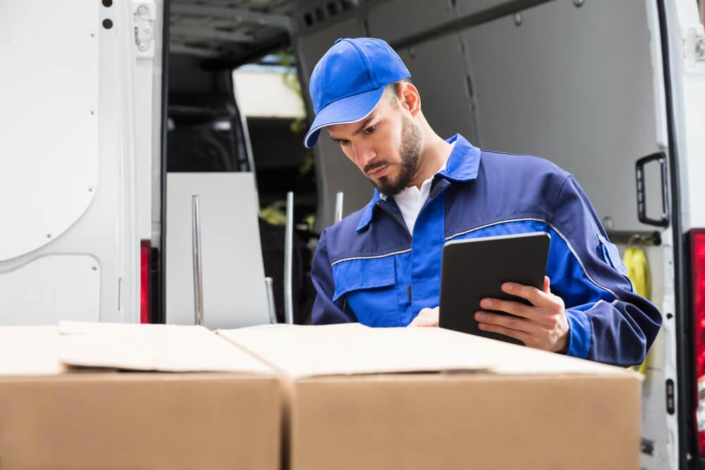equipe externa de logística utilizando apontamento eletronico para checar pacotes