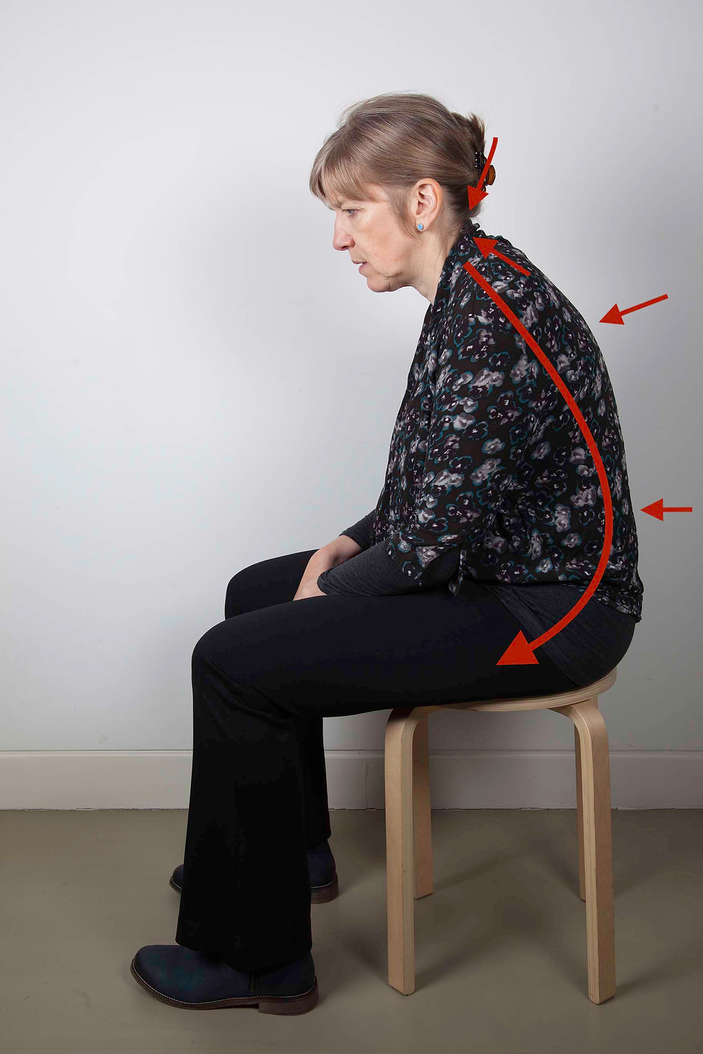 Sitting in a slumped position, weight on base of spine, causing the next to tighten and back to push out and lose natural lumbar curve