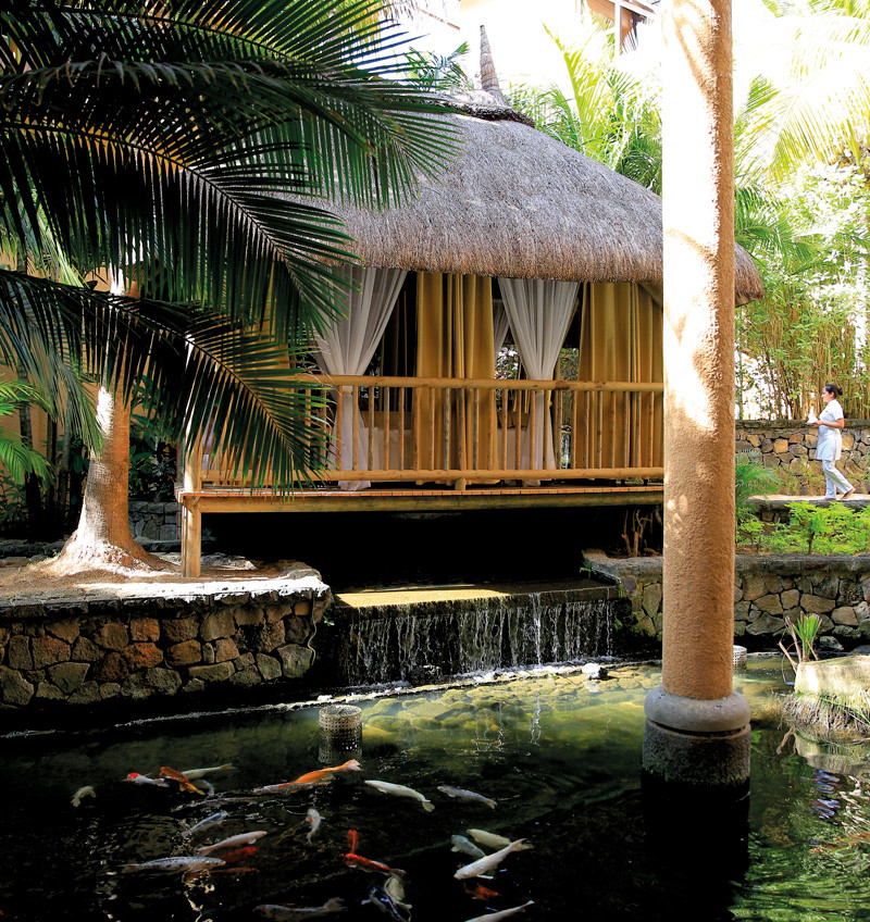 Wooden bamboo spa cabin overlooking palm trees and waterfall