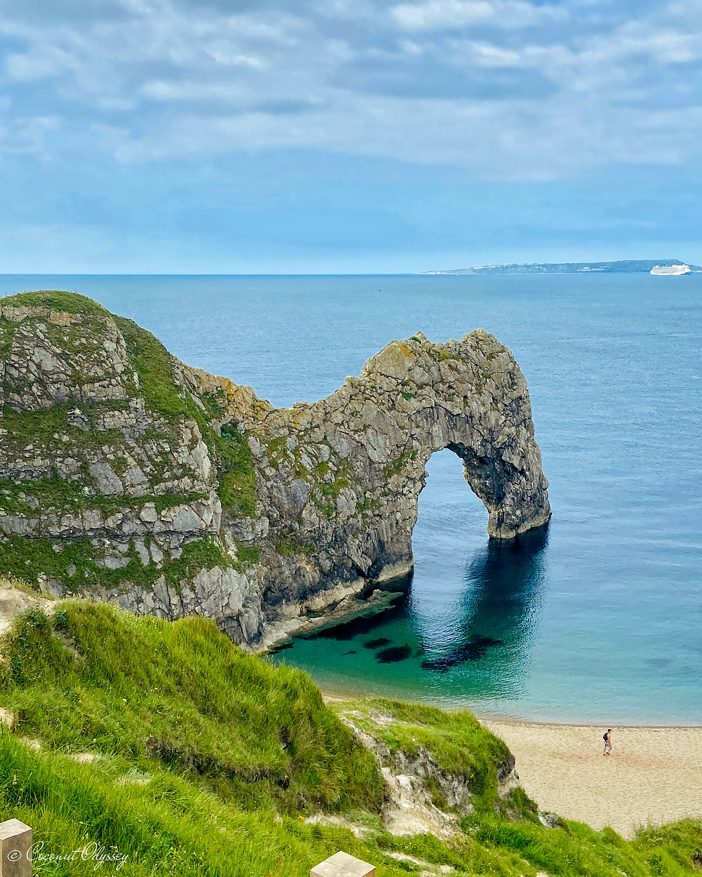 The famous Durdle Door Arch, naturally cut from grey limestone with lush green grassy cliff tops
