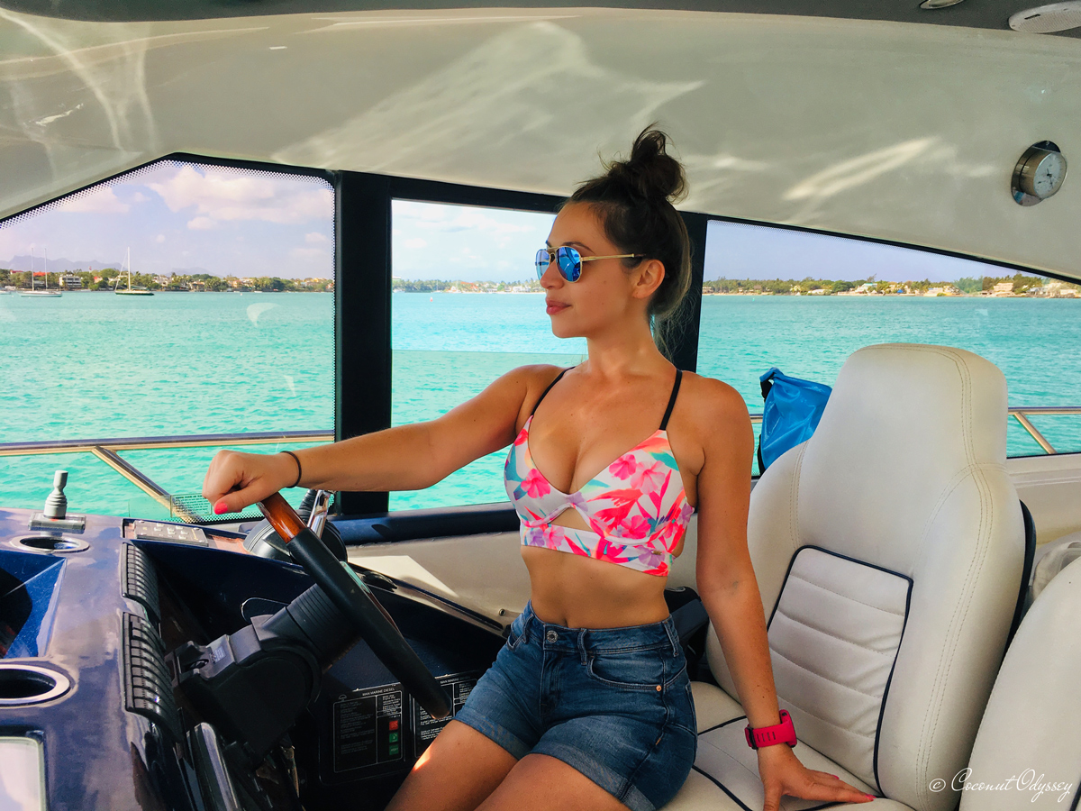 Girl in denim hot pants and pink floral push up bikini top sitting behind the wheel of a 64ft Royal Princess yacht