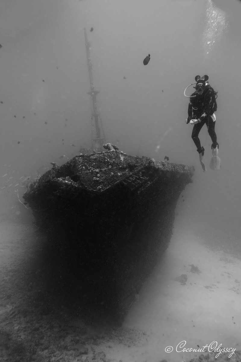black and white photo of a scuba diver with Minnie Mouse ears next to a ship wreck
