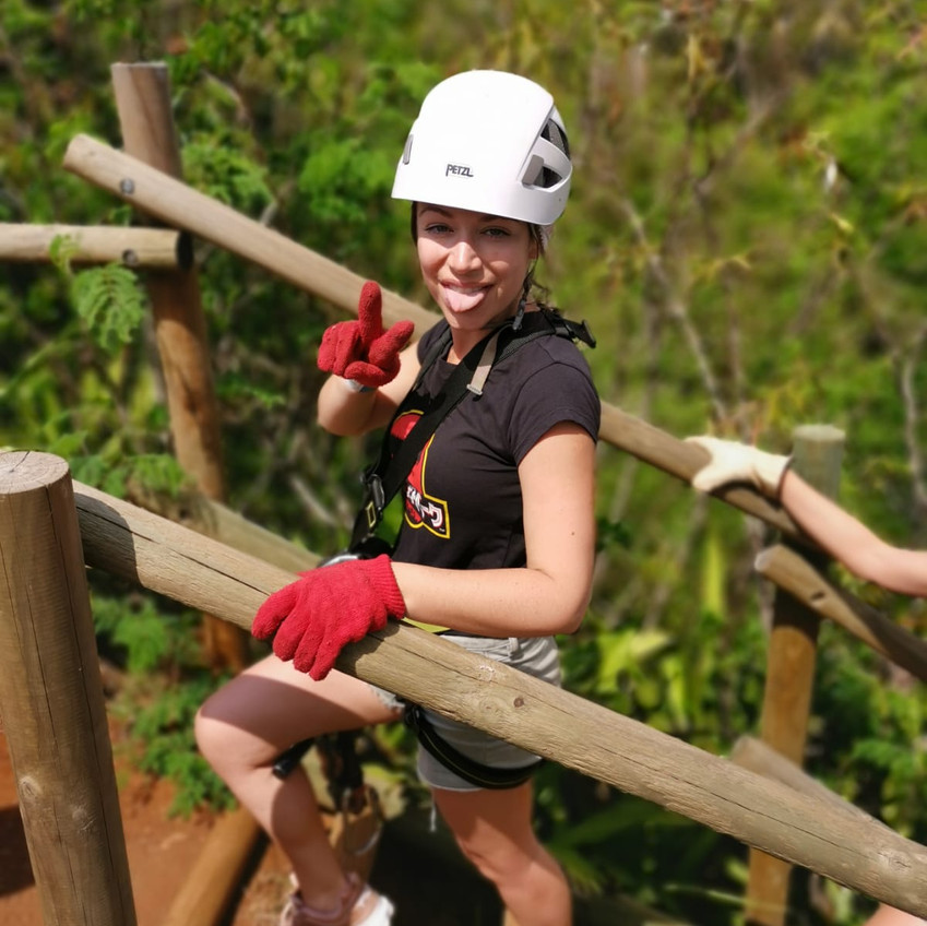 Girl in helmet excited and sticking out tongue after zip lining in Mauritius