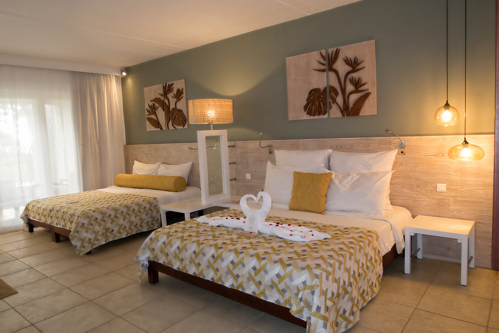 Deluxe group floor room with two king size beds, yellow decor and towels shaped like swans