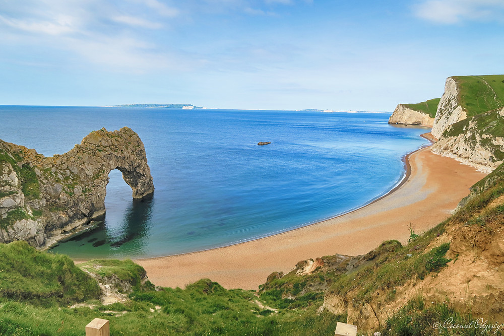 A photo of Durdle Door which forms part of the Jurassic Coast in Dorset. A natural eroded arch sits in the sea with a backdrop of white cliffs and a long stretch of golden pebbles
