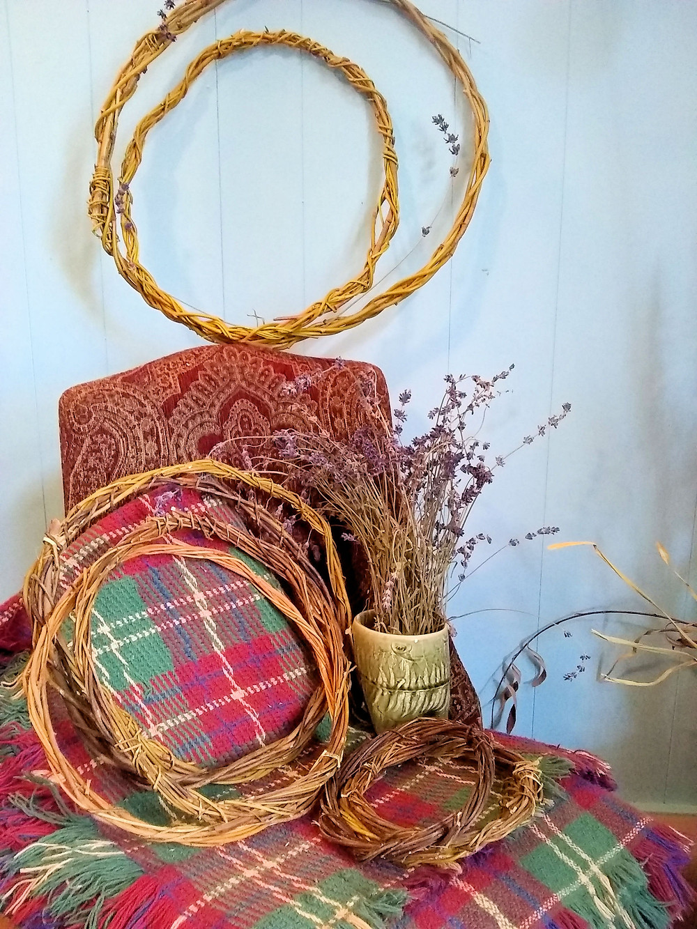 Golden Weeping Willow wreaths in varying sizes arranged against a tapestry chair.