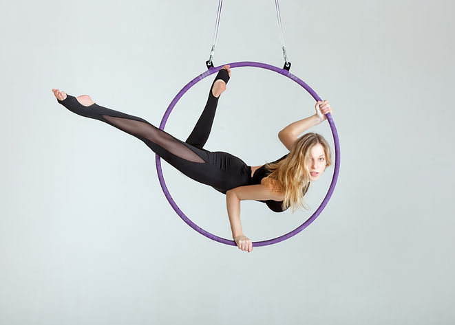 Woman aerial acrobat performs with trick