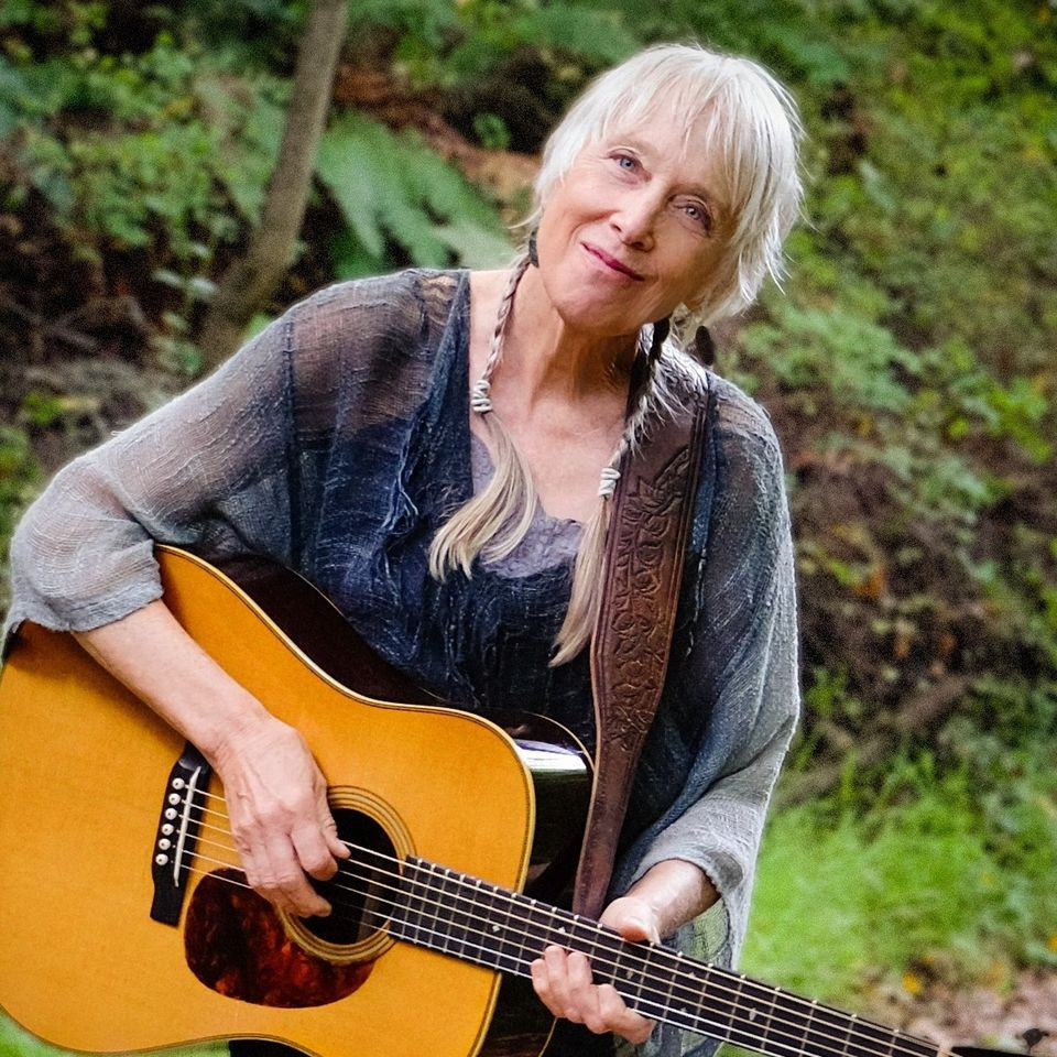 Photo of Laurie Lewis outside playing the guitar, smiling at the camera