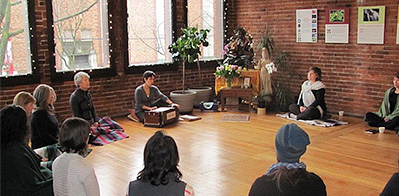 A photo from the website of Yasodhara Yoga of a group of people sitting around in a circle doing yoga