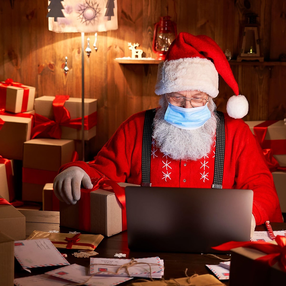 Photo of Santa Claus in his office, checking his naughty and nice lists on his laptop while wearing a mask and gloves
