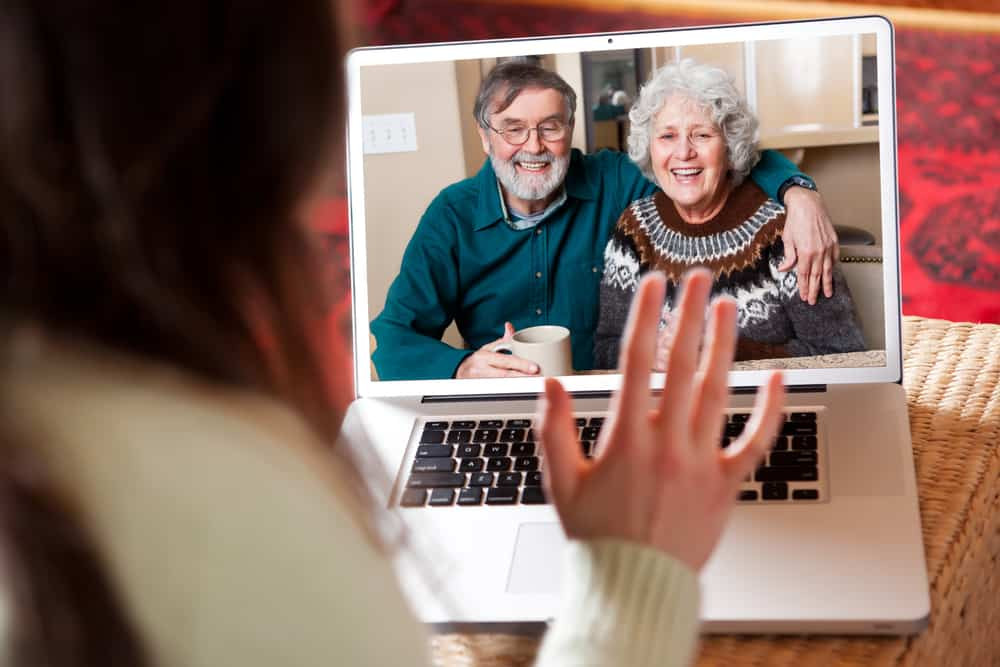 A young woman is video chatting with her grandparents on her laptop