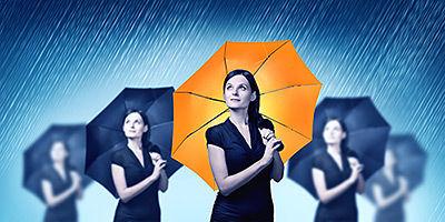 νέες γυναίκες με ομπρέλες σε γαλάζιο χρώμα και μπροστά μια ξεχωρίζει με ομπρέλα σε πορτοκαλί χρώμα.