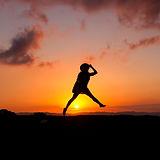 אישה קופצת באוויר על רקע שקיעה