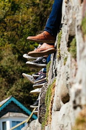 זוגות רגליים של כשישה אנשים שיושבים יחד על גדר לבנים, שותפים וחברים בקואופרטיב