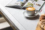 כוס קפה ומאפה ליד ספר פתוח של ספרות מומלצת
